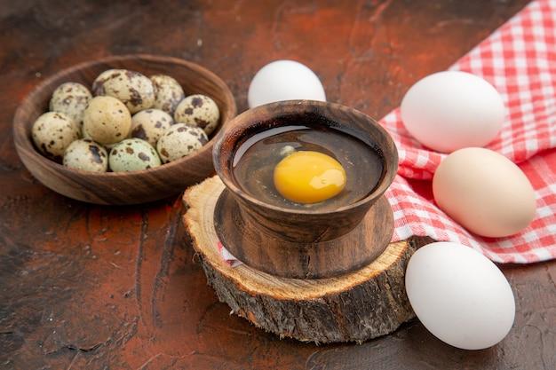 Vista frontale dell'uovo crudo rotto all'interno del piatto con pollo e uova di quaglia su superficie scura dark