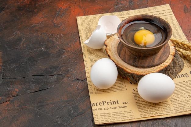 Вид спереди разбитое сырое яйцо внутри тарелки с другими яйцами на темной поверхности