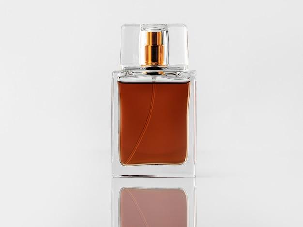 Una bottiglia marrone vista frontale con fragranza e con tappo dorato sulla scrivania bianca