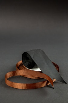 Front view brown bow with black bow on dark surface darkness pin measure photo color