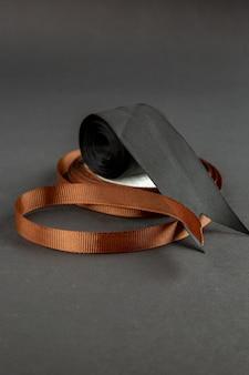 Вид спереди коричневый бант с черным бантом на темной поверхности темнота булавка мера для шитья фото цвета