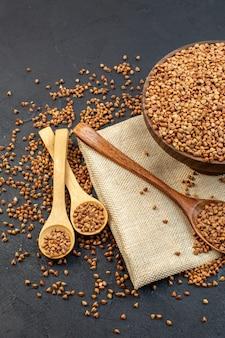 Vista frontale grano saraceno marrone piatto interno con un paio di cucchiai su sfondo scuro