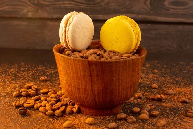 Una vista frontale semi di caffè marrone all'interno del piatto marrone con macarons sul granello di grano scuro del seme di caffè marrone