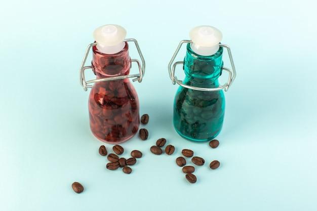 Una vista frontale marrone semi di caffè all'interno di barattoli di vetro colorato sulla superficie blu