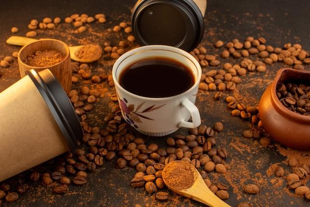 Una vista frontale semi di caffè marrone con barrette di cioccolato e tazza di caffè su tutta la superficie scura e granuli di chicchi di caffè