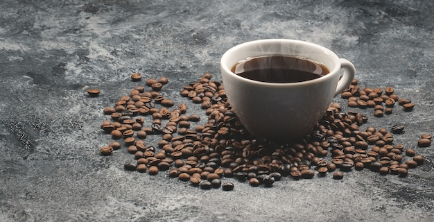 Front view of brown coffee seeds with cup of coffee on dark surface