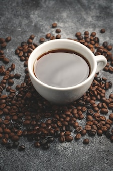 Front view of brown coffee seeds with cup of coffee on dark wall