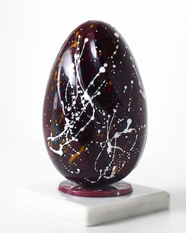 Front view brown egg with white lines on the white floor