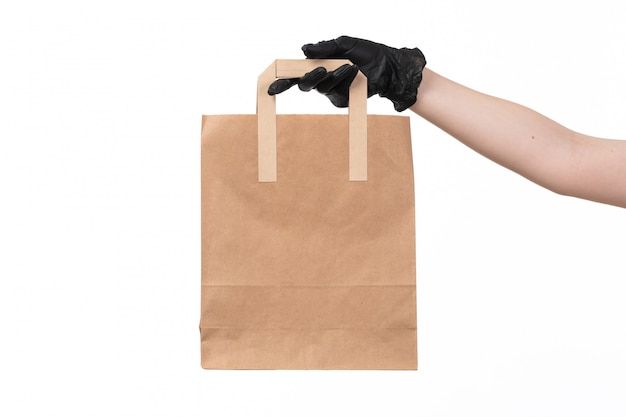 A front view brown paper package holding by female in black gloves job