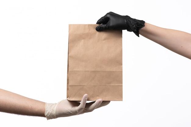 Un pacchetto di carta marrone vista frontale con cibo all'interno che viene consegnato da femmina a maschio