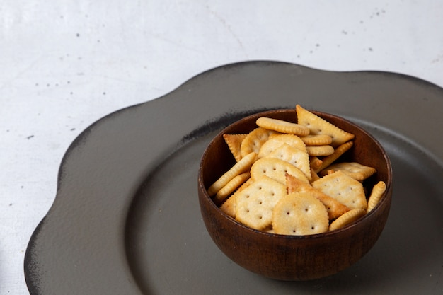 Front view of brown plate with crackers and crisps on the light surface