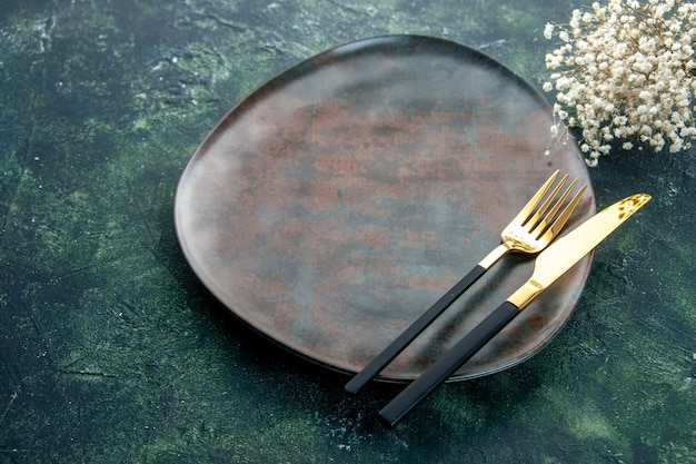 Front view brown plate with golden cutlery on dark blue background
