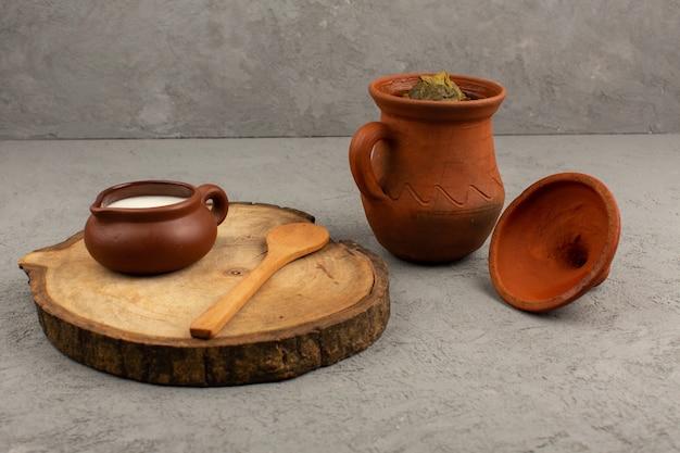 회색 바닥에 돌마와 요구르트로 디자인 된 갈색 냄비