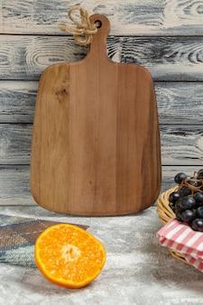 Вид спереди коричневый деревянный стол с оранжевым и темным виноградом на светлом фоне спелые свежие фрукты