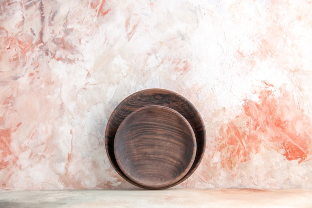 Front view of brown wooden plates in different sizes standing on wall on colorful surface