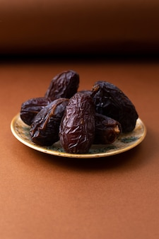 茶色の木製の机の上の正面の茶色xurma甘いおいしいプレート