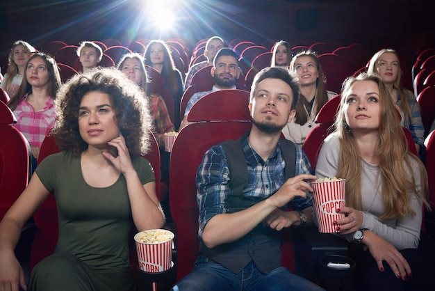 Front view of brunette girl and couple near sitting and hugging each other at cinema hall. pretty girlfriend and handsome boyfriend eating popcorn and enjoying of interesting movie.