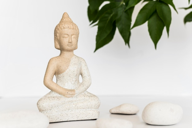 Front view of buddha statuette with stones and leaves