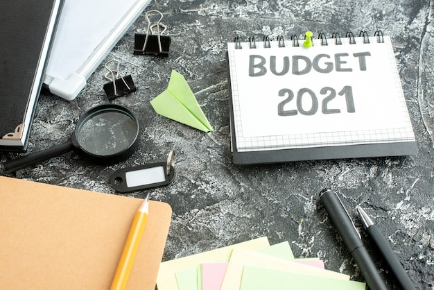 Nota di bilancio vista frontale con penne su sfondo grigio