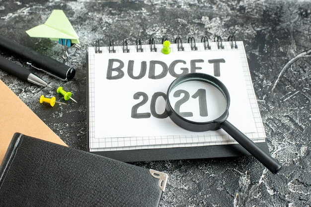 Front view budget note with pens and magnifier on dark background