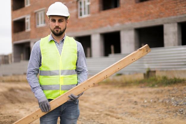 Front view builder man holding batten