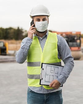 Front view builder man talking on phone