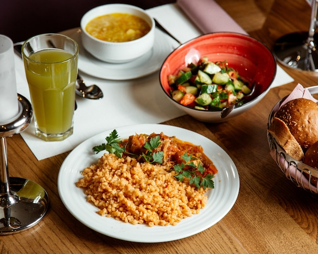 Front view bulgur with meat and sauce with vegetable salad soup and juice on the table