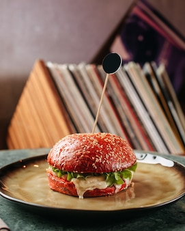 A front view burger red tasty fried inside plate on the light wall