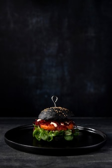 Front view burger with black buns and copy-space