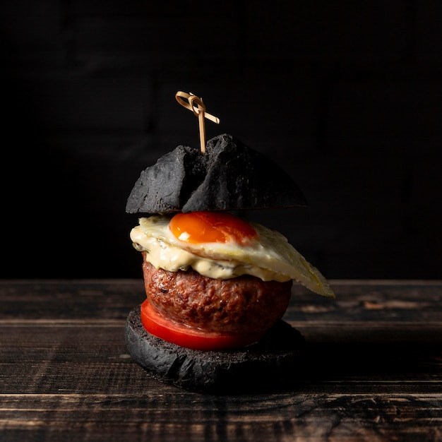 Front view burger with egg on table