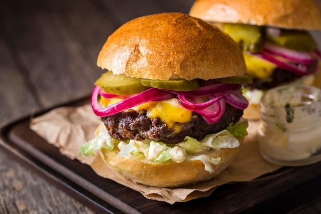 Hamburger di vista frontale con sottaceti sul tagliere