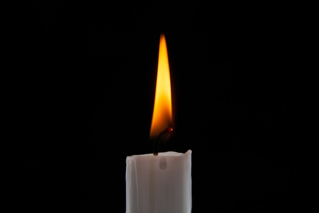 Front view burning candle on dark surface