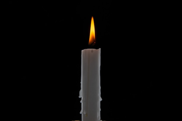 Front view of burning candle on dark surface