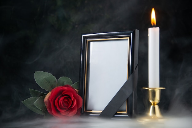 Front view of burning candle with picture frame on a black surface