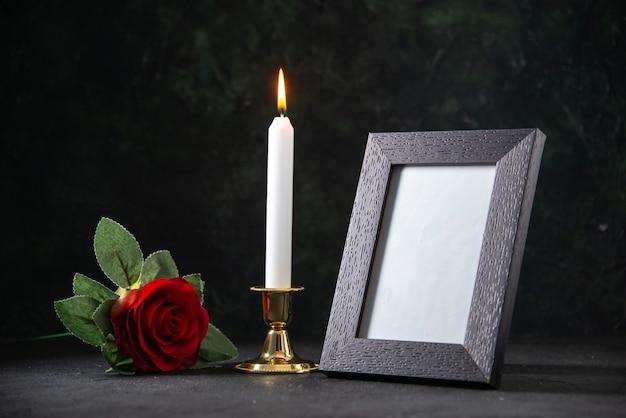 Vista frontale della candela accesa con cornice sulla superficie scura