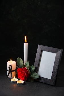 Candela accesa vista frontale con cornice e fiore sulla superficie scura