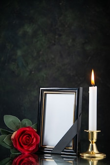 Front view of burning candle with red flower on black surface