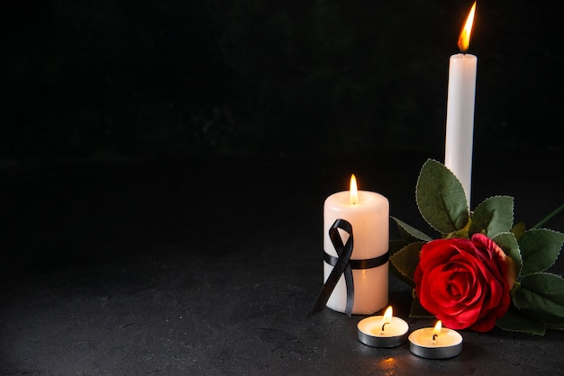 Front view of burning candle with red flower on dark surface