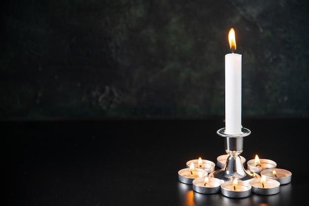 Vista frontale candele accese come memoria per i caduti sulla superficie nera