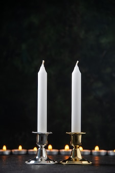 Front view of burning candles as memory for fallen on dark surface