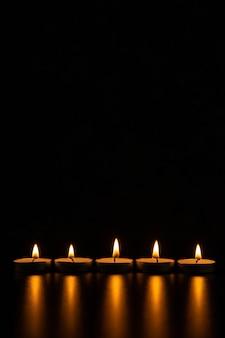 Vista frontale di candele accese sulla superficie nera come la pece