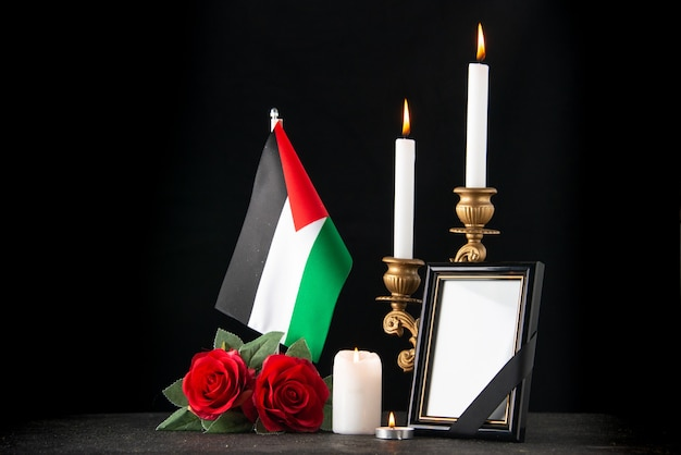 Front view of burning candles with palestinian flag on dark surface