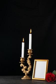 Vista frontale di candele accese con cornice come memoria sulla superficie scura
