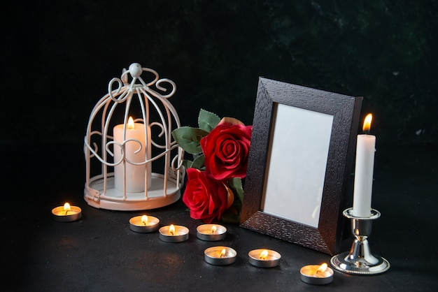 Front view burning candles with picture frame as memory for fallen dark surface