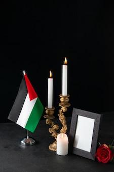 Vista frontale di candele accese con cornice sulla superficie scura