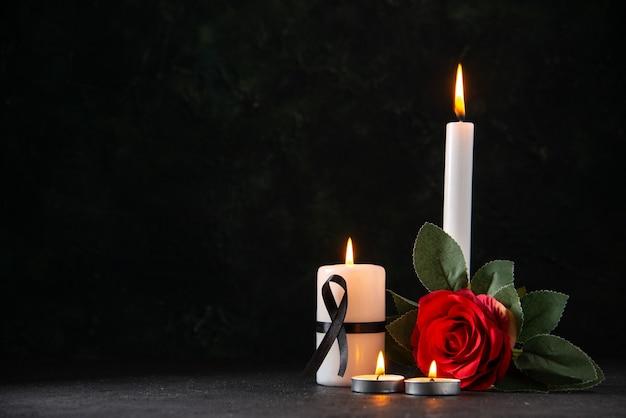 Vista frontale di candele accese con fiore rosso sulla superficie scura