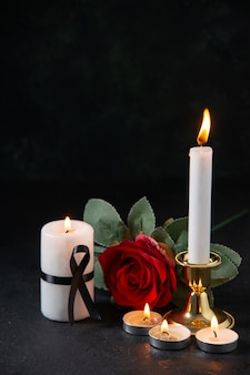 Front view of burning candles with red flower on dark surface