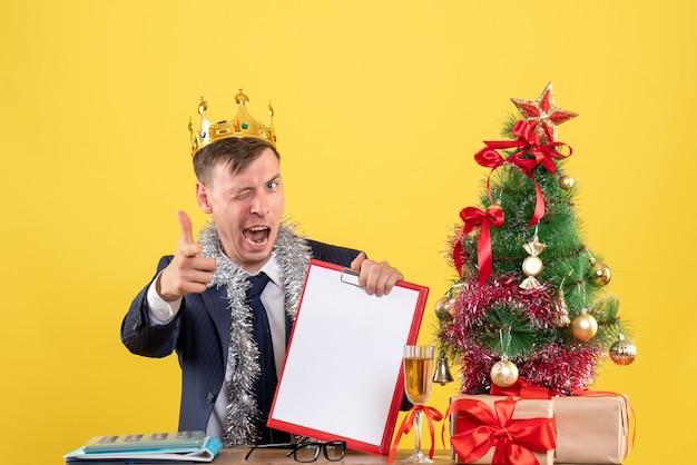 Вид спереди деловой человек мигает глазом, сидя за столом возле рождественской елки и представляет на желтом фоне