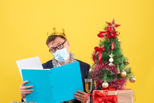 Uomo di affari di vista frontale che controlla i documenti che si siedono al tavolo vicino all'albero di natale e regali su fondo giallo