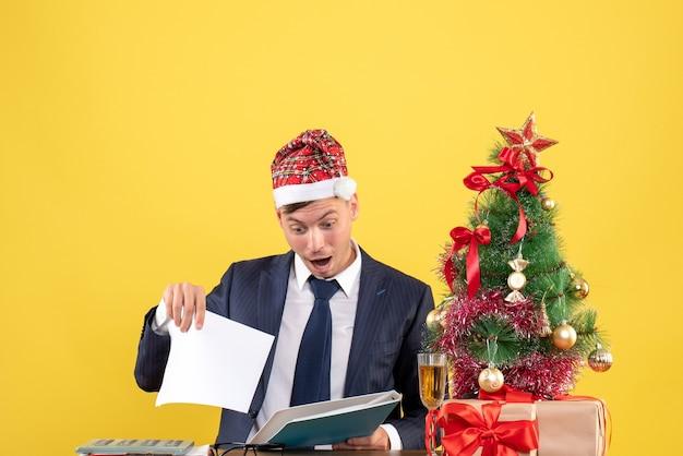 Vista frontale dell'uomo di affari che controlla i documenti che si siedono al tavolo vicino all'albero di natale e presenta sulla parete gialla